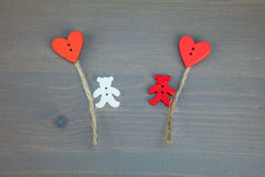 Two bears with balloons-hearts on grey wooden background. Stock Photo