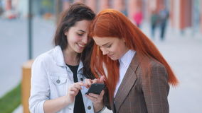 Two beatiful youthful girls weared in business style with swaying wind in the hair laughing and looking in smartphone. With urban landscape background stock video