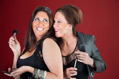 Two Beauties. Two giggling cougers dressed in black prepare their makeup Stock Images