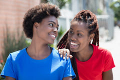 Two beautiful african american woman talking in city Stock Image
