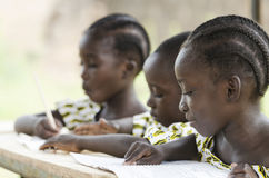 Two beautiful African girls and one African boy reading and writ. Ing at school as an educational symbol outside their school in Bamako, Mali. Beautiful Royalty Free Stock Photos