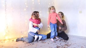 Two beautiful American moms sitting on floor and hugging with little daughters. Two young mothers from American family sitting on floor in living room and stock video footage