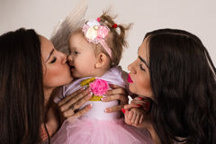 Two beautiful angels kissing little baby Stock Photo