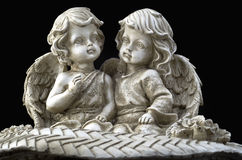 Two beautiful angels sitting. On the black background royalty free stock photography