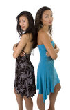 Two Beautiful Asian-American Women Back To Back. Two beautiful Asian-American women standing back to back with arms folded. Isolated on white Royalty Free Stock Photography