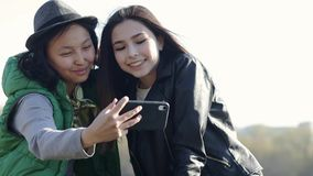 Two beautiful Asian teenage girls are making a funny selfie stock video