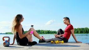 Two beautiful, athletic blonde girls, women have rest after training outdoors, drink water, talk, laugh. Lake, river stock footage