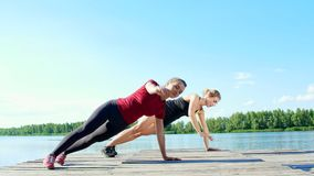 Two beautiful, athletic blonde women, doing coordination and balance exercises synchronously. Lake, river, blue sky and stock video