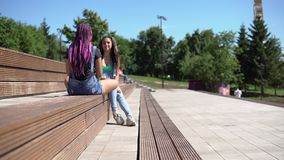Two attractive girlfriends talking to each other having a good mood sitting on a bench in the park. Two beautiful attractive girlfriends talking to each other stock video footage