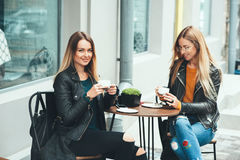 Free Two Beautiful Attractive Stylish Women Are Sitting Outdoor In Cafe Drinking Coffe And Tea Talking And Enjoying Great Day. Stock Photos - 98438023
