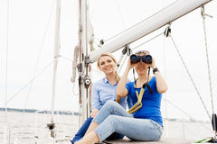 Two beautiful, attractive young girls with binocular on a yacht. Stock Image
