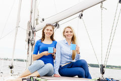 Two beautiful, attractive young girls drinking coffee on a yacht. Traveling, vacation, tourism, concept Stock Photos