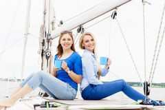 Two beautiful, attractive young girls drinking coffee on a yacht Royalty Free Stock Photography