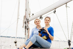 Two beautiful, attractive young girls drinking coffee on a yacht Royalty Free Stock Image