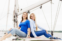 Two beautiful, attractive young girls a hiving a rest on yacht. Royalty Free Stock Image