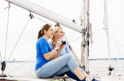 Two beautiful, attractive young girls taking pictures on a yacht Royalty Free Stock Photo