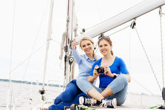 Two beautiful, attractive young girls taking pictures on a yacht Stock Photo
