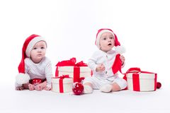 Two beautiful baby in the New Year`s cap and white body sitting. Among festive boxes with gifts and Christmas balls, picture with depth of field stock images