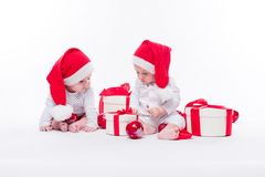 Two beautiful baby in the New Year`s cap and white body sitting. Among festive boxes with gifts and Christmas balls, picture with depth of field royalty free stock photography