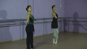 Two beautiful ballerina dancing. In the classroom stock video footage