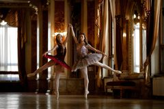 Two beautiful ballerinas dancing in a luxurious hall royalty free stock photos