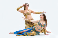 Two beautiful belly dancers. Dressed in gold and blue, isolated Stock Photography