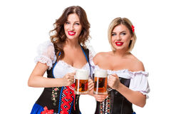 Two beautiful blond and brunette girls of oktoberfest beer stein Stock Image