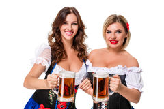 Two beautiful blond and brunette girls of oktoberfest beer stein Royalty Free Stock Photos