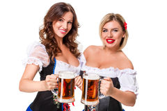 Two beautiful blond and brunette girls of oktoberfest beer stein Royalty Free Stock Image