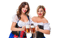Two beautiful blond and brunette girls of oktoberfest beer stein Stock Photo