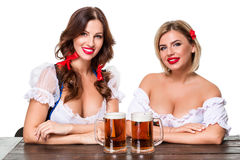 Two beautiful blond and brunette girls of oktoberfest beer stein Stock Photos