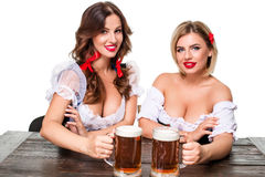Two beautiful blond and brunette girls of oktoberfest beer stein Royalty Free Stock Photography