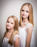 Two Beautiful Blond Teenage Girls Dressed in White. Royalty Free Stock Image