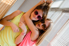 Two beautiful blond teenage girls having fun happy. Closeup portrait of hugging 2 beautiful blond young women having fun happy smiling on sunny windows Stock Image