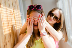 Two beautiful blond teenage girls having fun happy. Closeup portrait of 2 beautiful blond young women having fun happy smiling closing eyes in surprise on sunny Stock Image