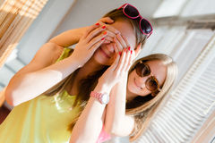Two beautiful blond teenage girls having fun happy smiling. Closeup portrait of 2 beautiful blond young women having fun happy smiling closing eyes in surprise Royalty Free Stock Photo