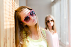 Two beautiful blond teenage girls standing in distance upset Royalty Free Stock Photo