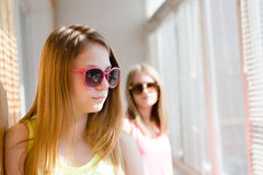 Two beautiful blond teenage girls standing in distance upset Royalty Free Stock Image