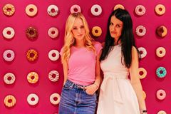 Two beautiful blonde and brunette girls closeup on the pink donut background stock photography