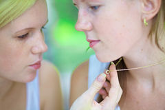 Two beautiful blonde girls look necklace Stock Images