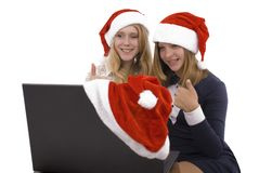 Two beautiful blonde in santa claus hat with laptop Royalty Free Stock Photography