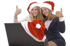 Two beautiful blonde in santa claus hat with laptop Stock Photo