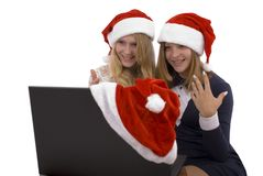 Two beautiful blonde in santa claus hat with laptop Royalty Free Stock Photos