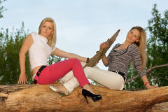 Two beautiful blonde sitting on a tree branch Stock Image