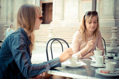 Two beautiful blonde women talking at the bar. In the city Stock Photos