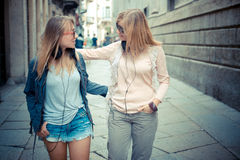 Two beautiful blonde women walking and talking Stock Photos