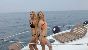 Two beautiful blondes in bikinis posing on yacht`s bow stock video footage