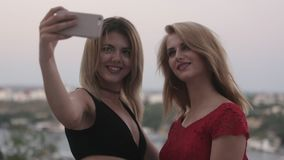 Two beautiful blondes in dresses making selfie on a mobile phone stock footage