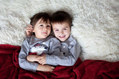 Two beautiful boys, brothers, lying down in bed, hugging, smiling at the camera. Shot from above royalty free stock image