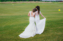 Two beautiful brides embracing on the green field royalty free stock photo